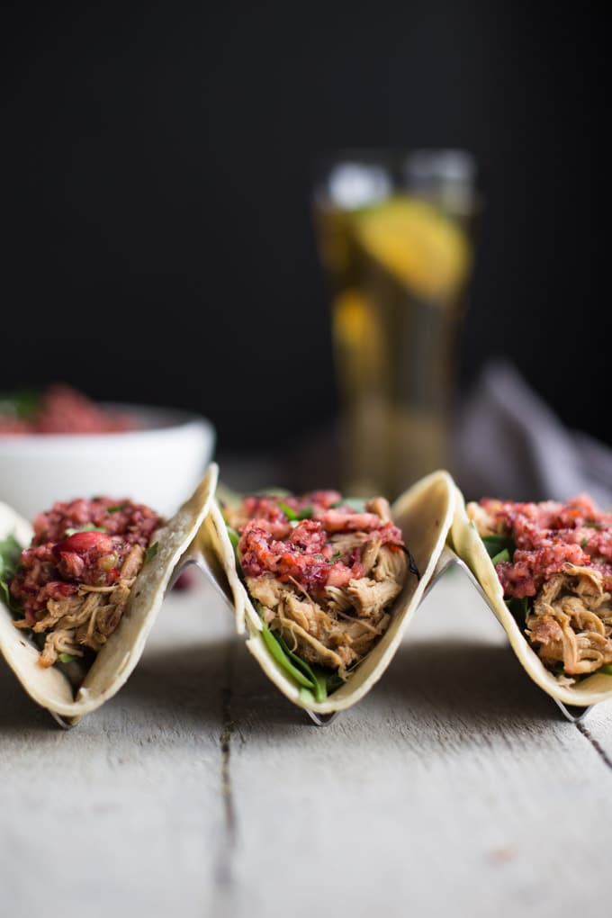 Side view of Slow Cooker Chicken Tacos with a dark background.