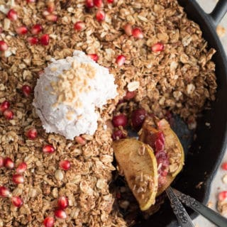 Overhead view of Apple, Cranberry and Pomegranate Oatmeal Crisp with coconut whip in a black cast iron pan.
