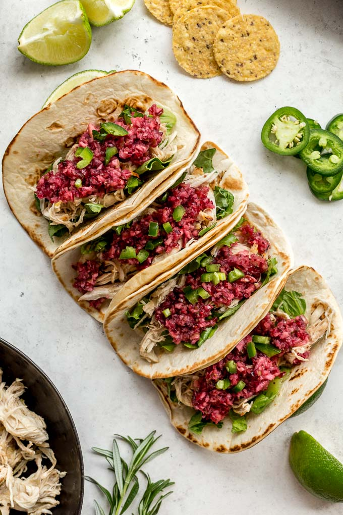 Up-close view of Slow Cooker Chicken Tacos topped with cranberry salsa.