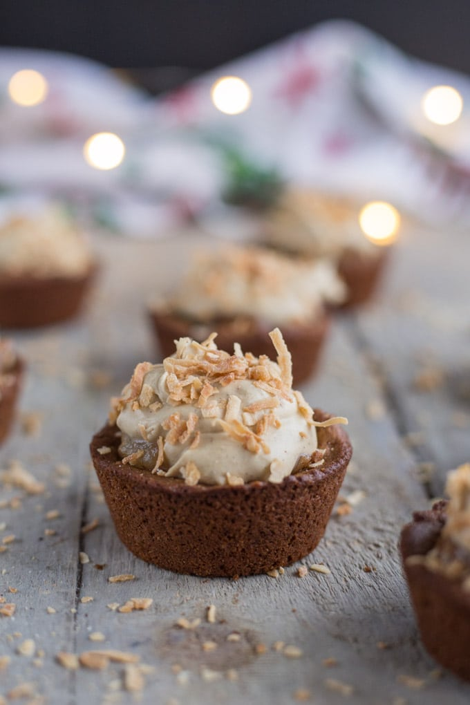 Side view of Spiced Pear Gingerbread Cookie Cups on a wooden surface.