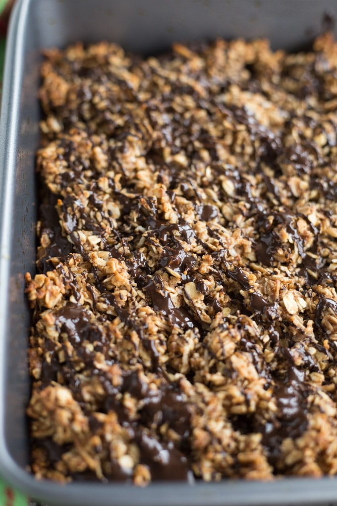 Up-close view of Chocolate Chai Spice Crumble Bars in a pan with chocolate drizzled on top.