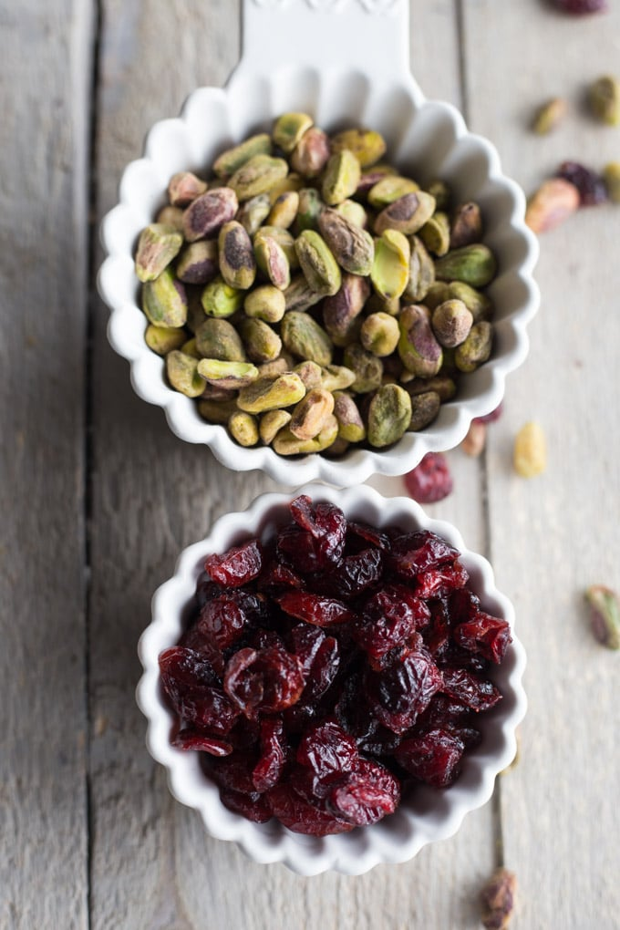 Cranberries and pistachios in individual white cups on a wooden surface.