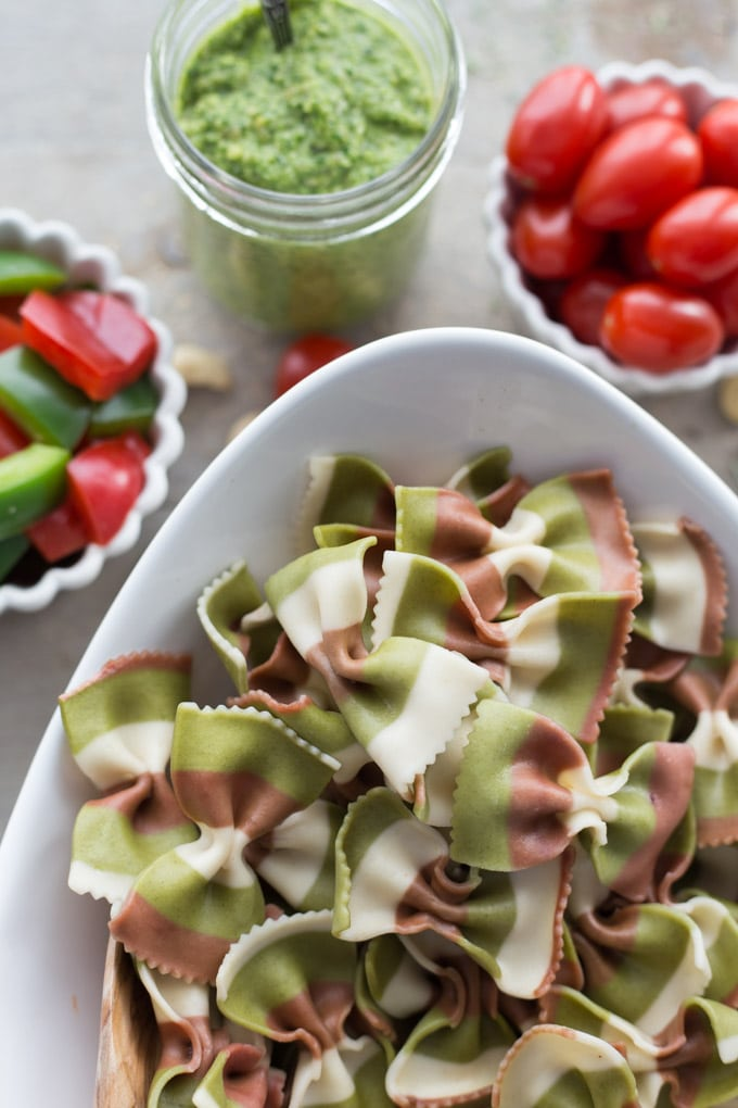 Up close view of bow-tie pasta with the pesto and veggies for Festive Pesto Pasta Salad in the background.