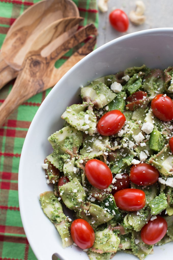 Overhead view of Festive Pesto Pasta Salad in a white bowl with wooden spoons and red and green napkin.