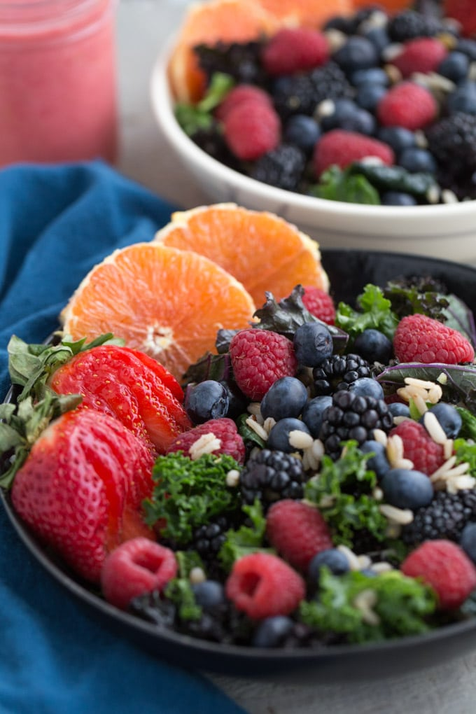 Up-close view of Berry Citrus Kale Salad in a black bowl.