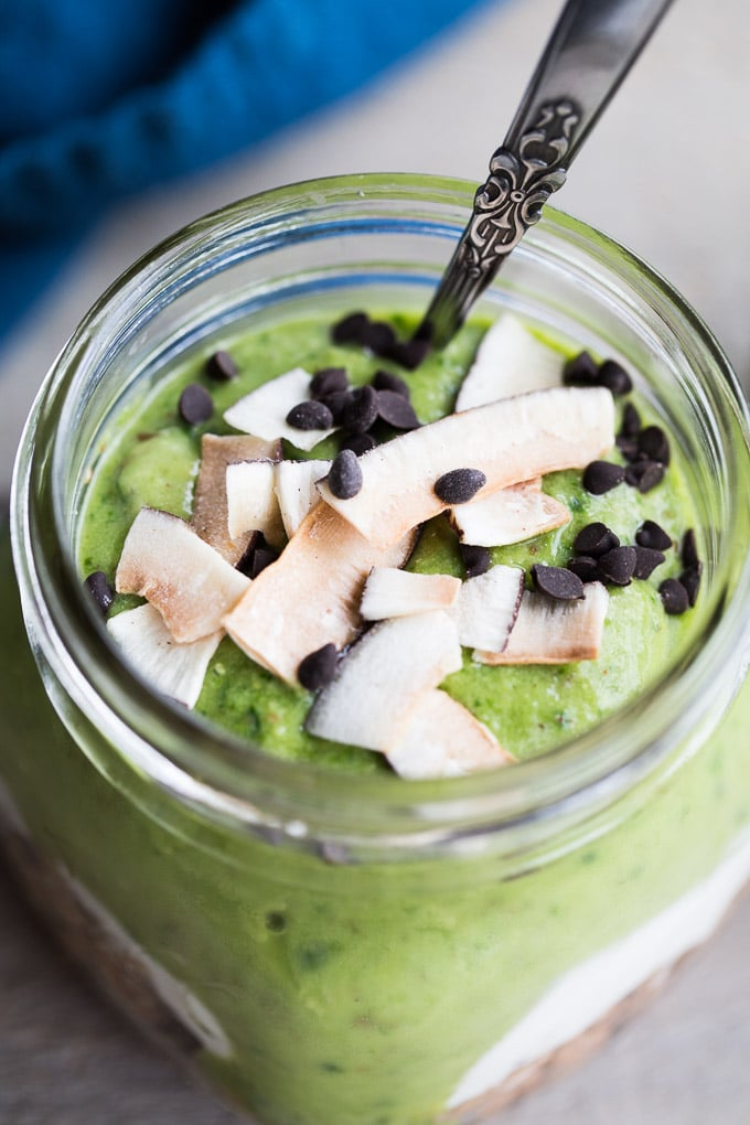 Older photo of a mango avocado oatmeal smoothie made with spinach - overhead view topped with coconut and chocolate chips.