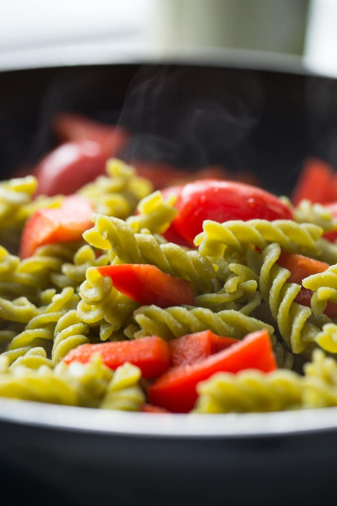 Up close view of cooked pasta in a black pan, tossed with tomatoes and red peppers, with steam rising from the pasta.