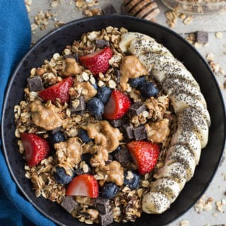 Overhead view of granola and fruit in a black bowl next to a blue napkin and on a wood surface.