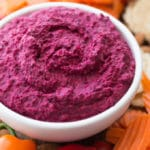 Up-close view of beet hummus in a white bowl with vegetables on the side