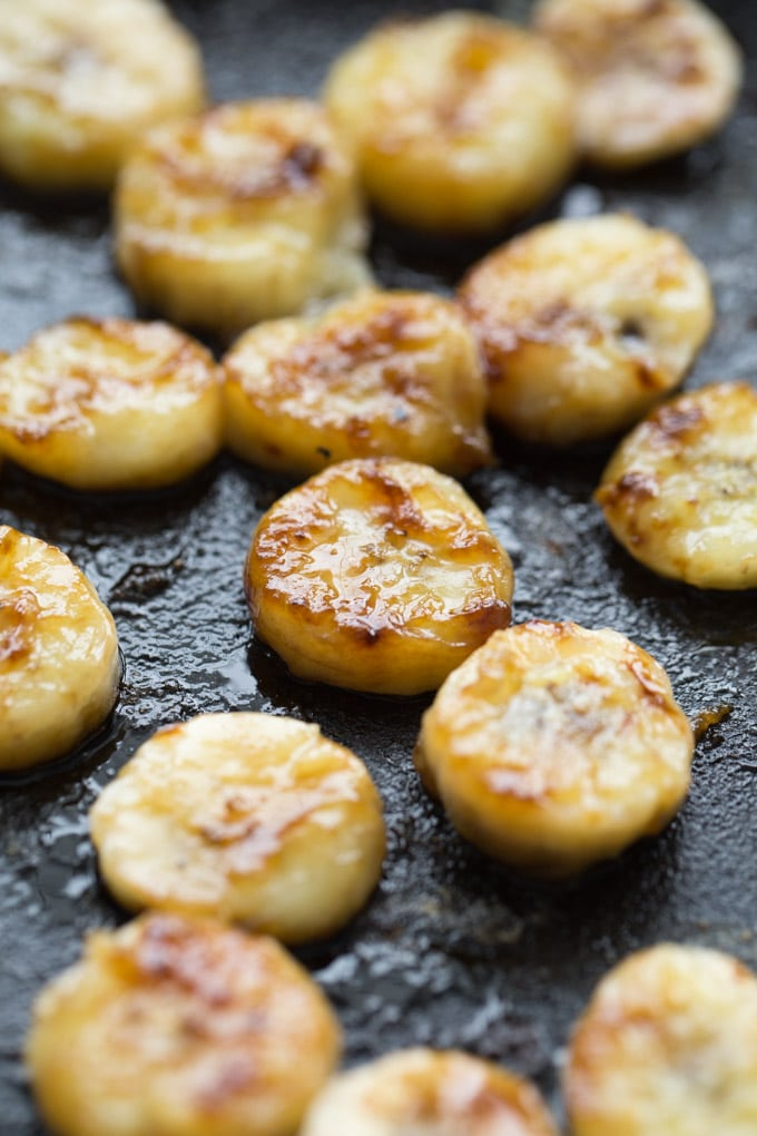 Up close view of caramelized banana slices in a cast iron frying pan.