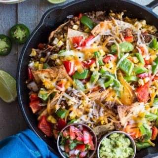 Overhead view of Loaded Vegetarian Nachos in a cast iron skillet on a wooden surface surrounded by jalapeño, lime and pico de gallo.