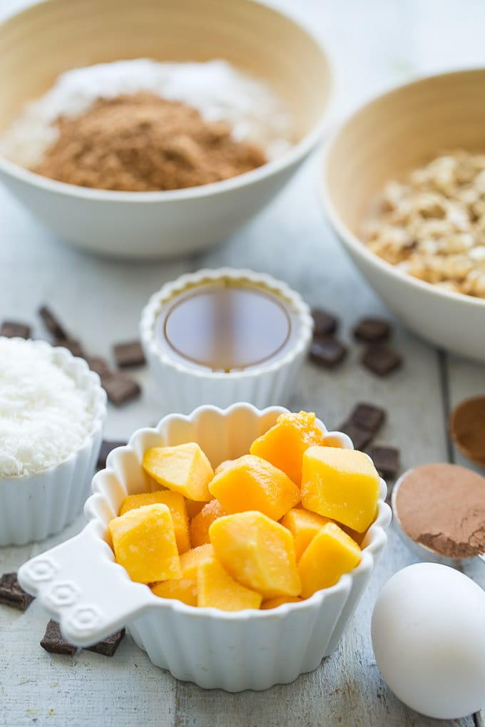 Ingredients for Coconut Mango Oatmeal Muffins spread out on a white wooden surface.