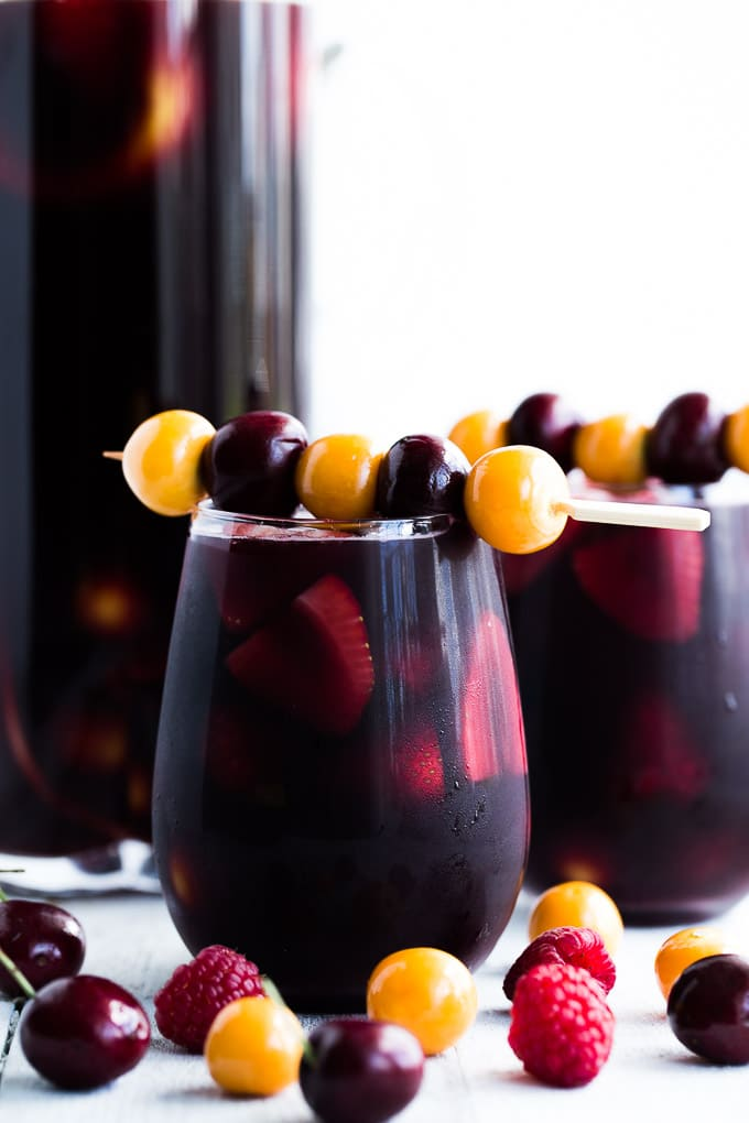 Up-close side view of Berry Cherry Kombucha Sangria in cocktail glasses and a pitcher.