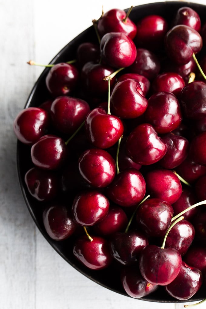 Overhead view of cherries in a black bowl on a white wooden surface.