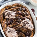 Up-close view of Dark Chocolate Cherry French Toast Bake out of the oven and topped with dark chocolate and cream.