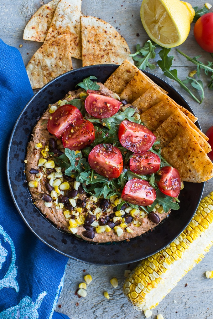 Older photo of a black bean hummus bowl on a wooden surface next to a blue napkin and other ingredients.