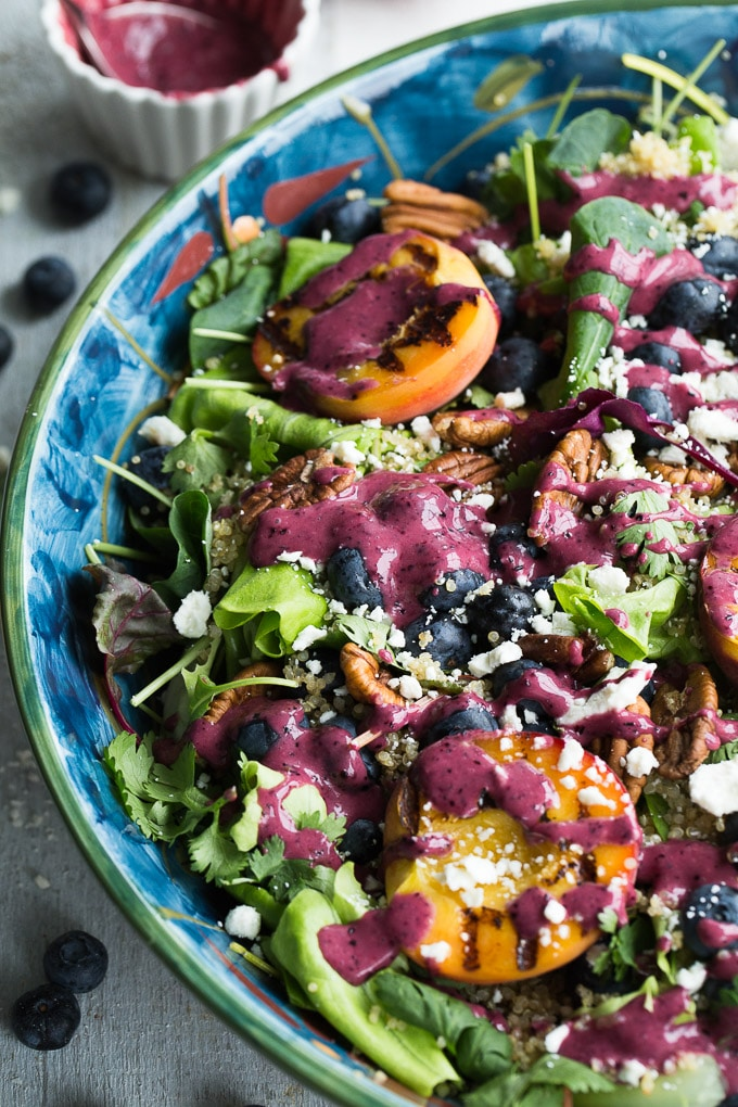 Up-close overhead view of Blueberry Peach Quinoa Salad in a blue bowl with the blueberry peach balsamic vinaigrette drizzled over the top.
