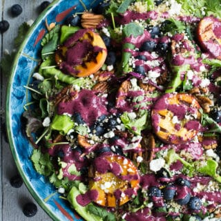 Overhead view of Blueberry Peach Quinoa Salad in a blue bowl on a wooden surface.