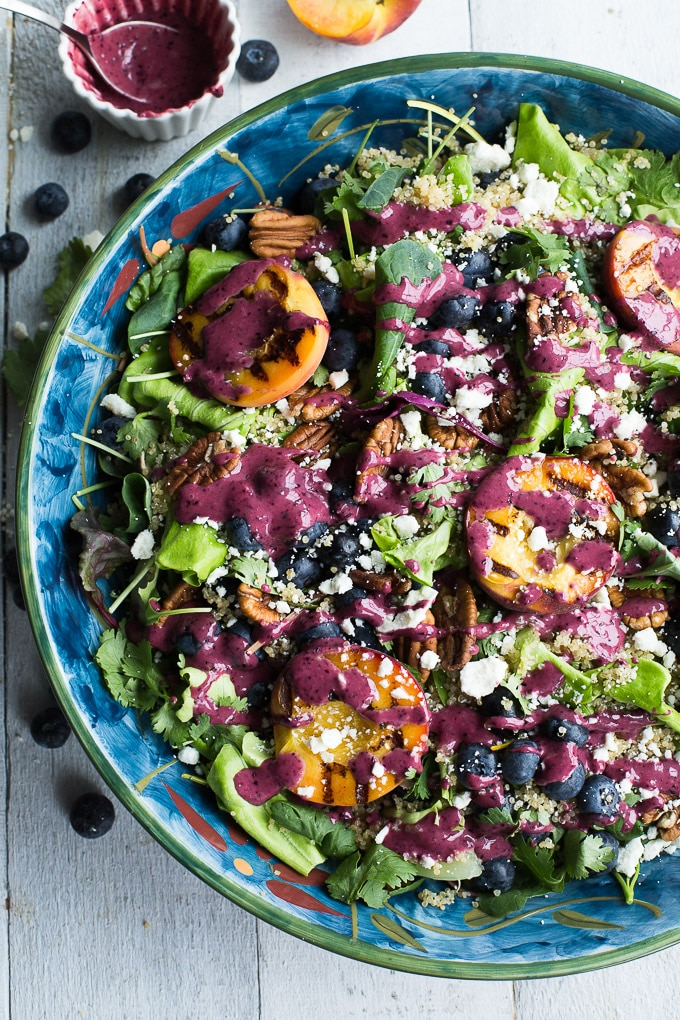Overhead view of Blueberry Peach Quinoa Salad in a blue bowl on a white wooden surface.