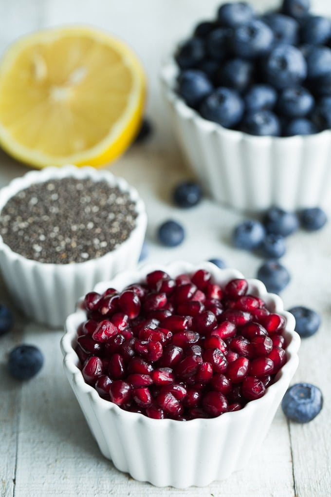 Ingredients for Blueberry Pomegranate Chia Jam in individual bowls on a wooden surface.