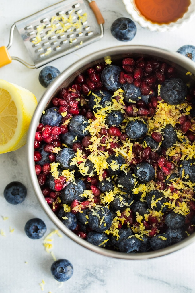 Overhead view of all the ingredients for Blueberry Pomegranate Chia Jam in a small sauce pan.