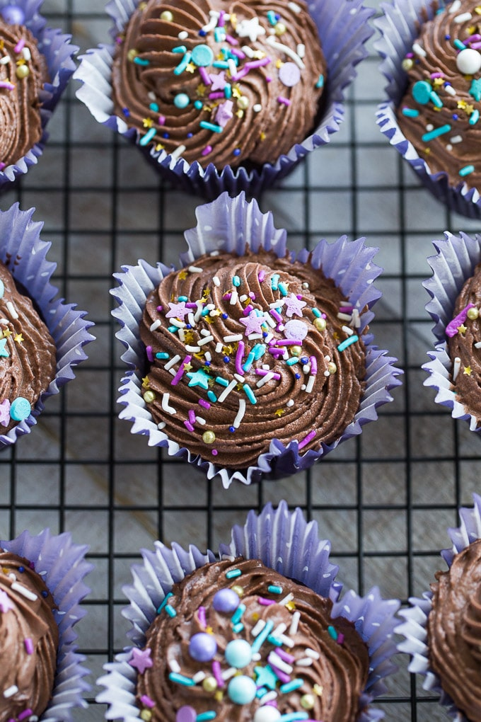 Overhead view of Chocolate Zucchini Cupcakes on a wire rack topped with coconut whip and sprinkles.