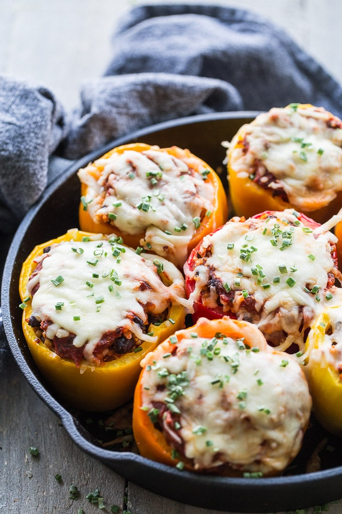 Up close view of baked Vegetarian Stuffed Peppers in a black cast iron pan.