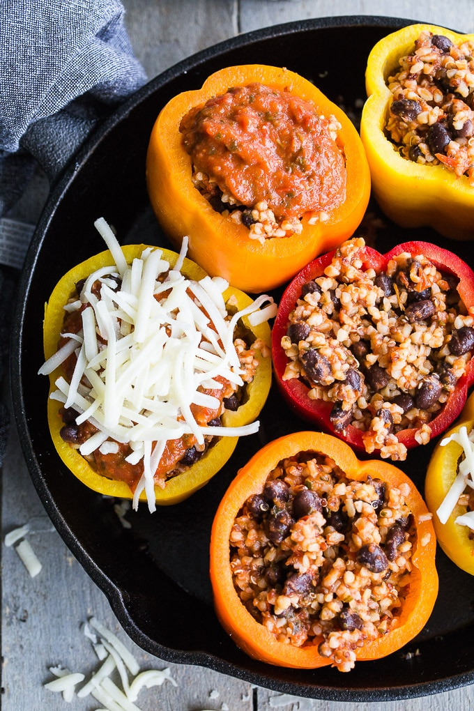 Overhead view of Vegetarian Stuffed Peppers being assembled in a black cast iron pan.