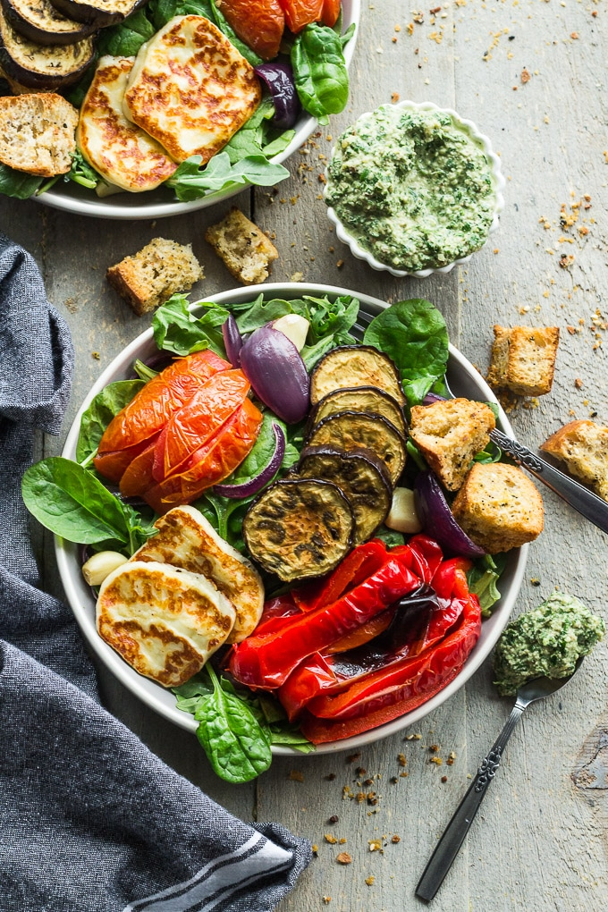 Overhead view of two plates of Salad with Roasted Vegetables and Halloumi Cheese next to a cup of pesto, croutons and a grey napkin.