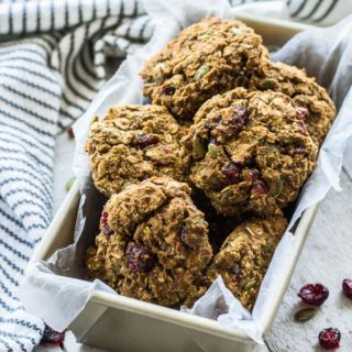 Up-close view of Avocado Pumpkin Oatmeal Breakfast Cookies arranged in a loaf pan on a wooden surface.