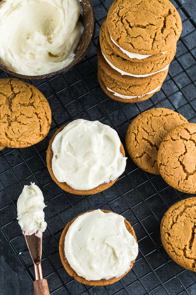 Overhead view of Chewy Ginger Cookies with Lemon Cream Cheese Frosting being assembled on a wire rack.