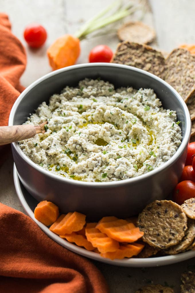Creamy Cashew Onion Herb Dip in a bowl surrounded by carrot slices, cherry tomatoes and crackers.