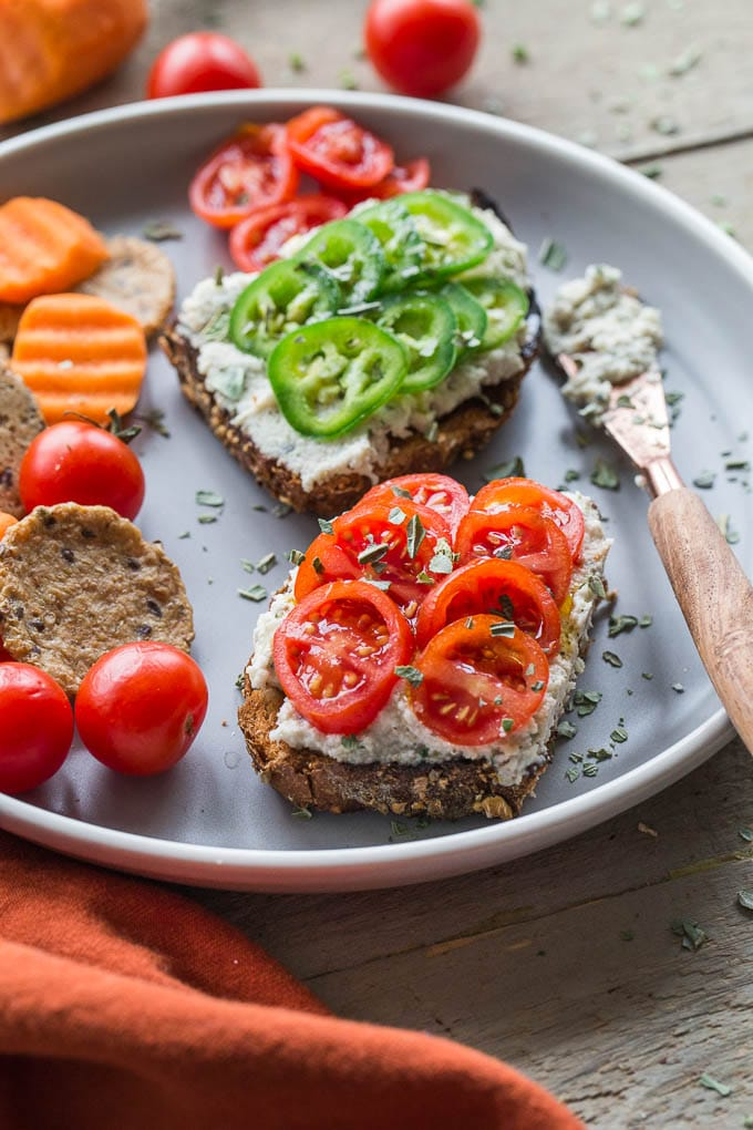 Side view of Creamy Cashew Onion Herb Dip spread on slices of bread with tomatoes and jalapeños on top.