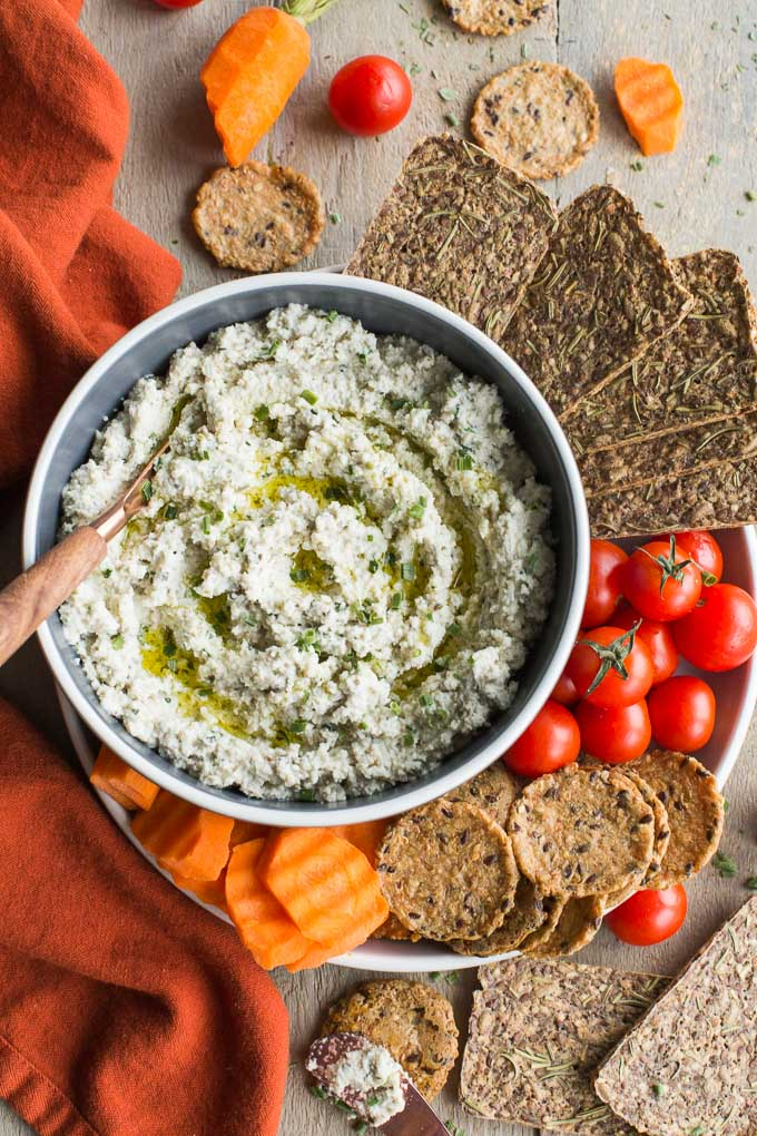 Overhead view of Creamy Cashew Onion Herb Dip in a bowl surrounded by carrots, tomatoes and crackers on a wooden surface.