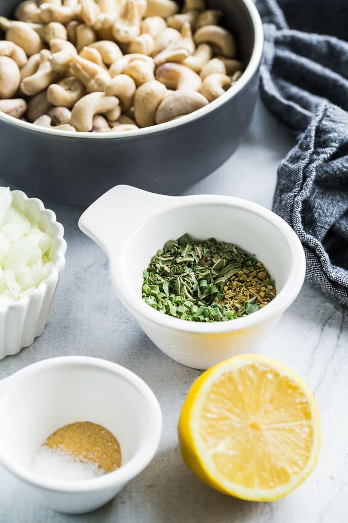 Ingredients for Creamy Cashew Onion Herb Dip arranged in individual bowls on a light coloured surface.