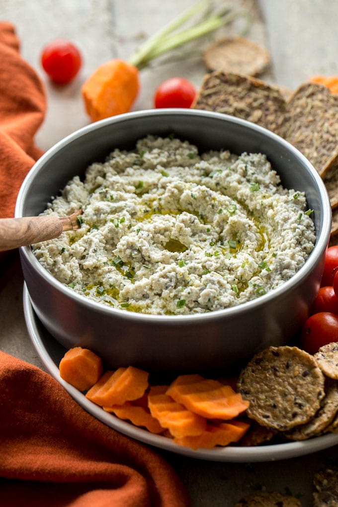 Older image of cashew onion herb dip in a bowl surrounded by crackers and veggies.