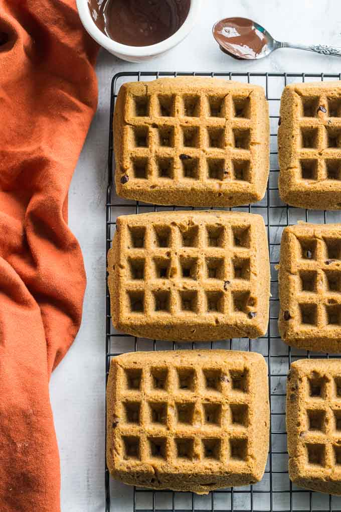 Overhead view of Grain-Free Pumpkin Chocolate Chip Waffles cooling on a wire rack next to an orange napkin and a dish of melted chocolate.