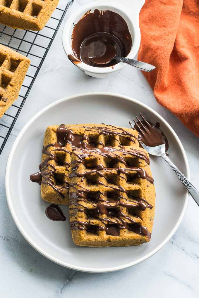 Overhead view of Grain-Free Pumpkin Chocolate Chips Waffles being served on a grey plate with melted chocolate drizzled over them.