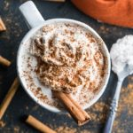 Overhead view of a Pumpkin Spice Collagen Latte on a dark surface surrounded by cinnamon sticks.