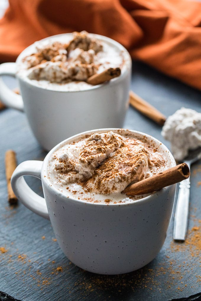 Side view of two mugs of Pumpkin Spice Collagen Lattes with coconut whip.