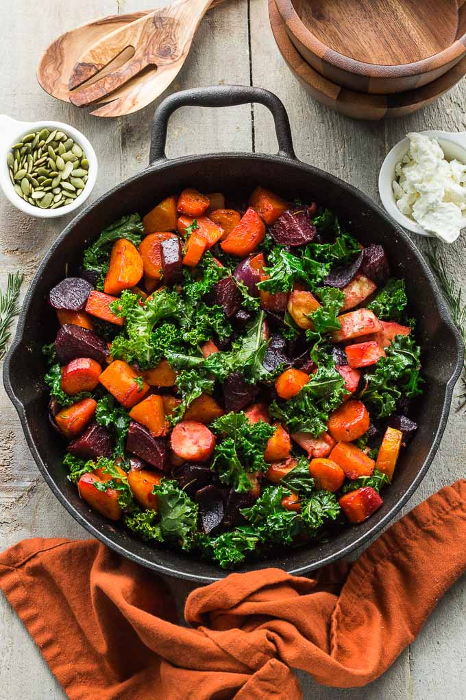 Overhead view of Rosemary Roasted Root Vegetables with Kale in a black cast iron pan on a wooden surface.