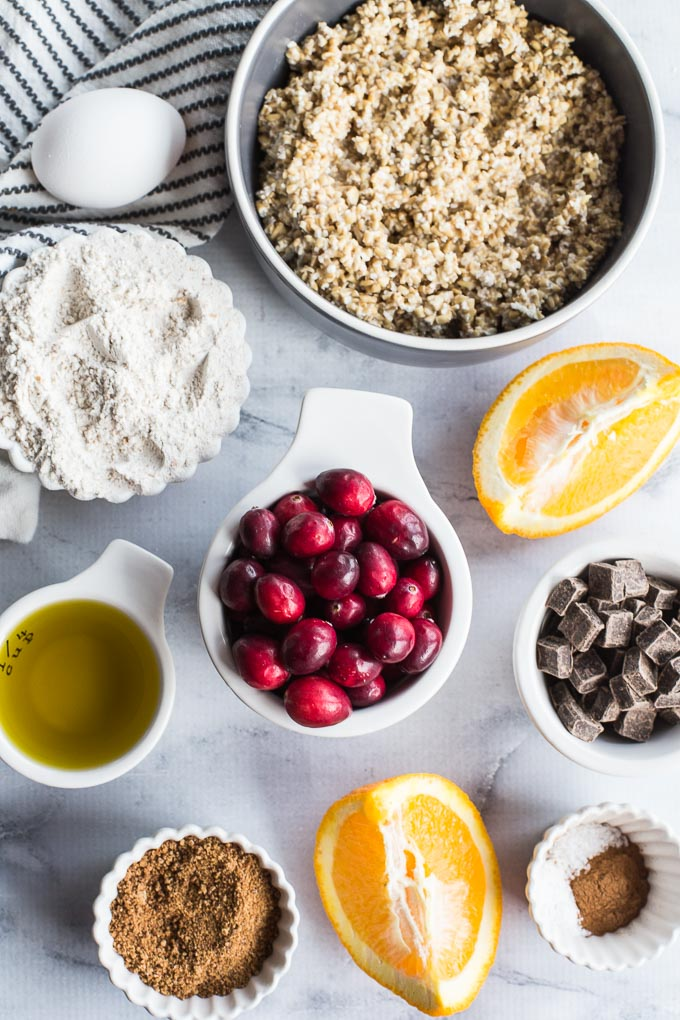 Ingredients for Cranberry Orange Overnight Oatmeal Muffins arranged in individual dishes.