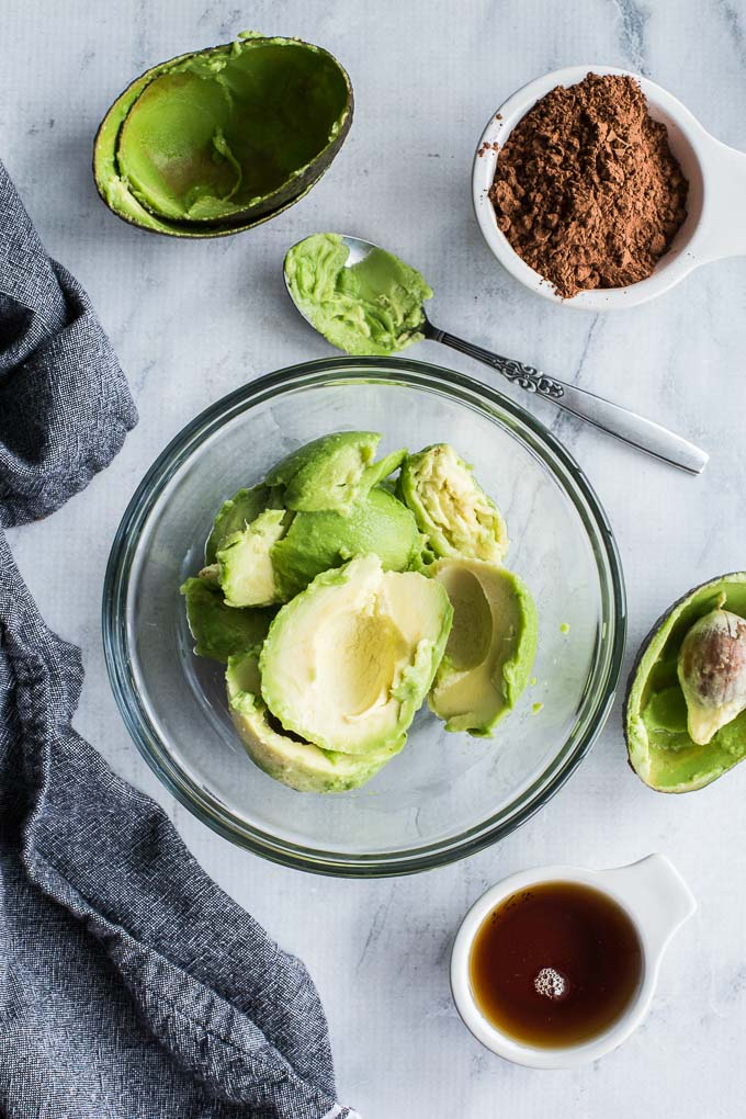 Overhead view of avocado in a glass bowl with measuring cups filled with cocoa and maple syrup off to the side.