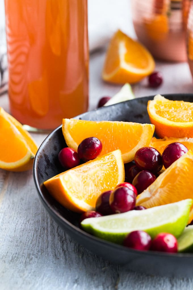Up-close view of cranberries and orange and lime wedges in a black bowl with kombucha in the background.