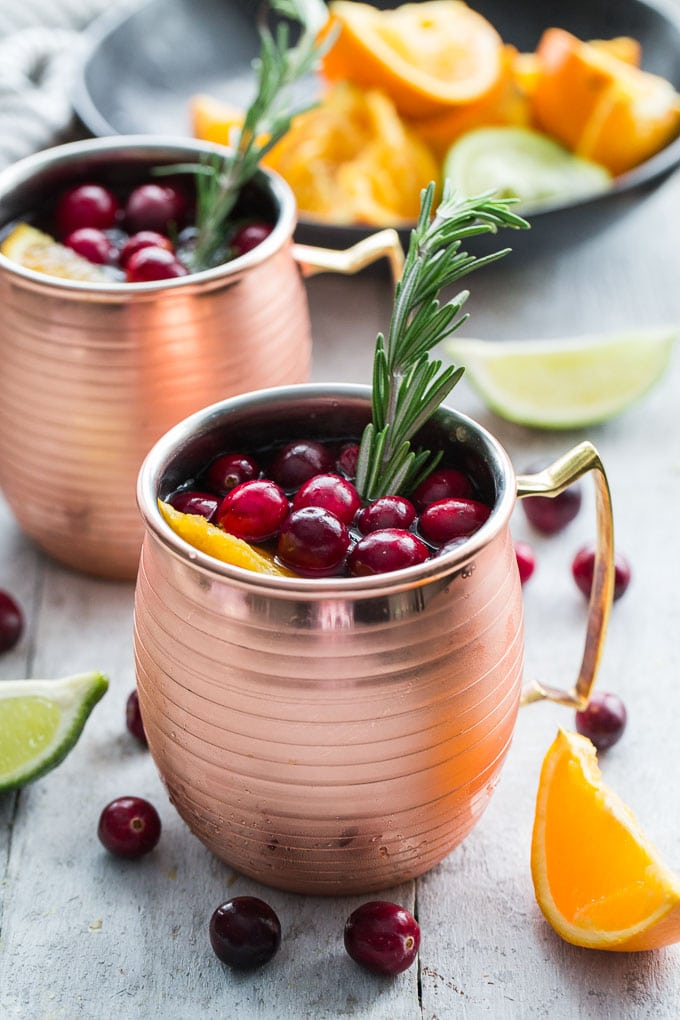 Orange Cranberry Kombucha Moscow Mules in copper mugs.