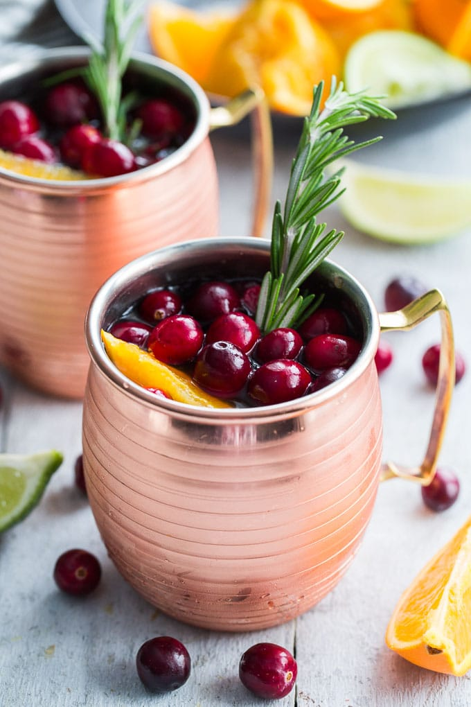 Side view of Orange Cranberry Kombucha Moscow Mule in copper mugs.