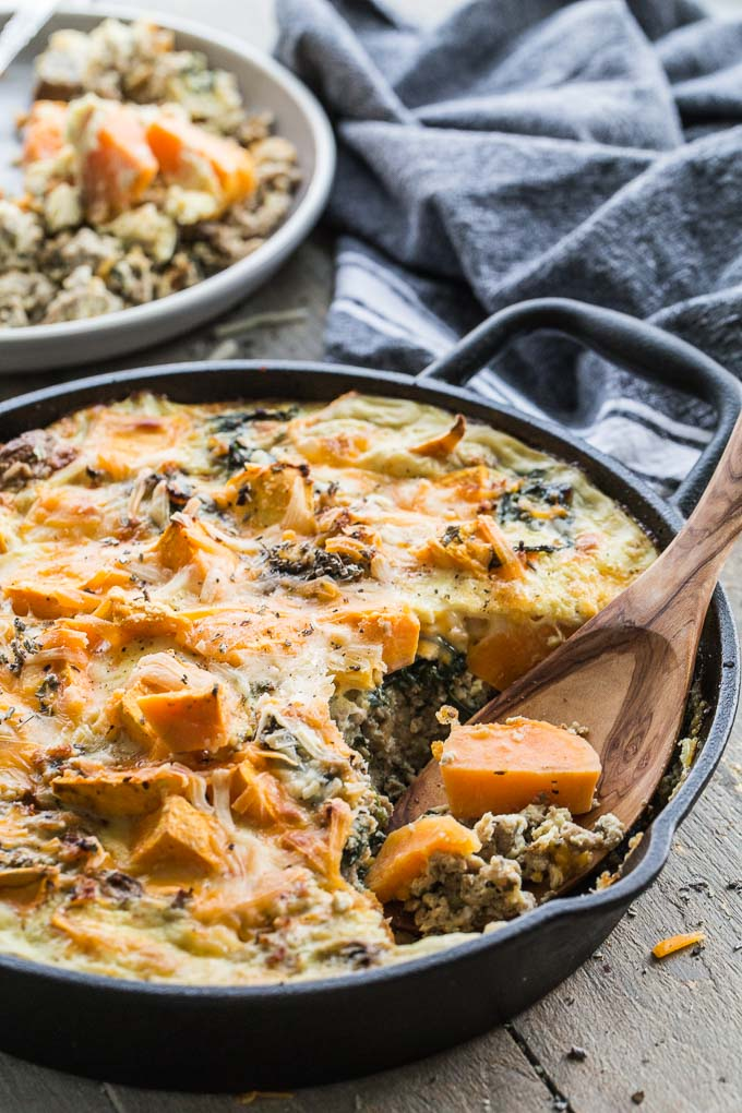 Sweet Potato Turkey Egg Bake in a cast iron skillet with a wooden spoon scooping some out.