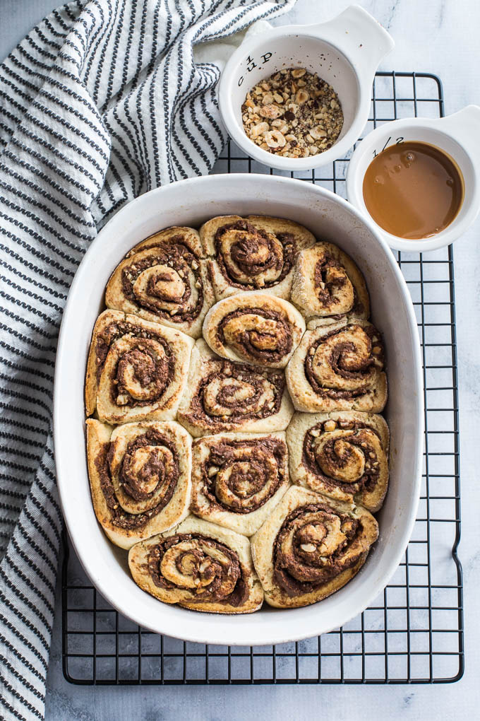 Overhead view of Chocolate Hazelnut Caramel Rolls in a white dish, cooling on a wire rack.