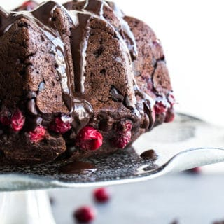 Side view of Dark Chocolate Cranberry Bundt Cake on a cake stand.