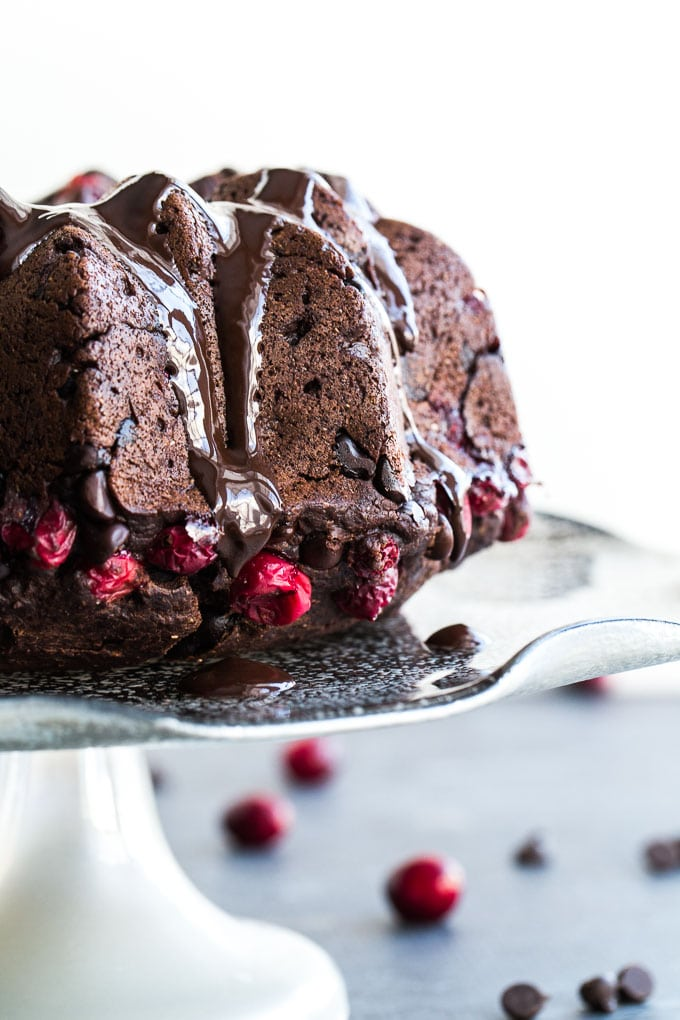 Older photo of a dark chocolate cranberry bundt cake - side view on a cake stand.